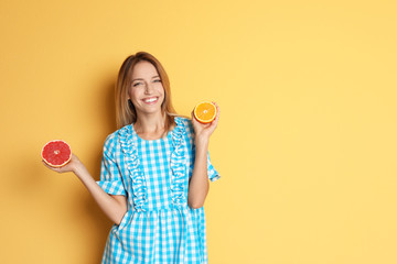 Happy slim woman with grapefruit and orange on color background. Weight loss diet