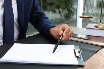 Male lawyer working with documents at table, closeup. Notary services