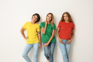 Group of young women in jeans and colorful t-shirts on light background