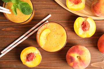 Tasty peach smoothie and fresh fruit on wooden background, top view
