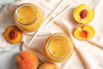 Tasty peach smoothie in glass jars on table, top view