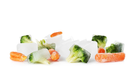 Frozen vegetables and ice cubes on white background