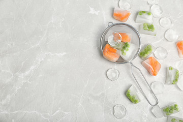 Frozen vegetables and ice cubes on gray table, flat lay composition with space for text