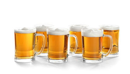 Glass mugs of beer on white background