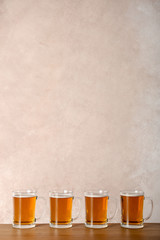Glass mugs with beer on table against color background