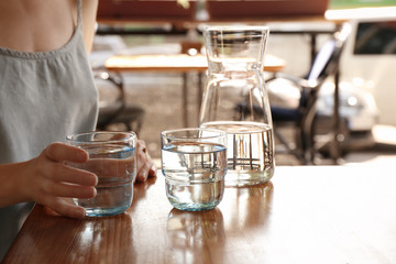 Woman with glass of water at table indoors