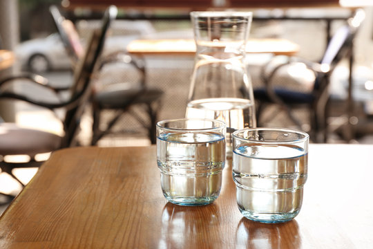 Glassware with water on wooden table indoors