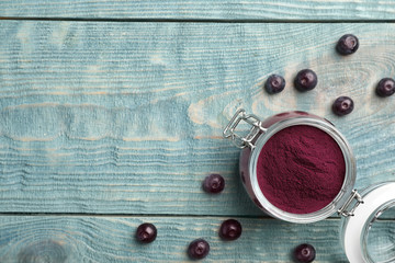 Jar of acai powder and fresh berries on wooden table, flat lay with space for text