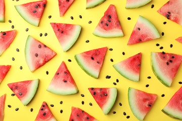 Flat lay composition with slices and seeds of watermelon on color background