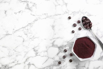 Bowl of acai powder and fresh berries on marble table, flat lay with space for text