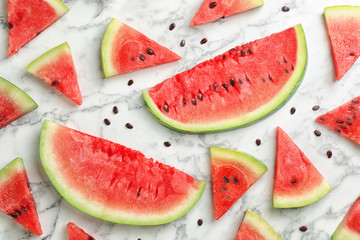 Flat lay composition with slices and seeds of watermelon on marble background