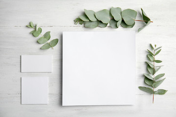 Fresh eucalyptus leaves and blank cards with space for design on wooden background, top view