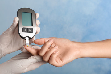 Doctor checking blood sugar level with glucometer on color background. Diabetes test