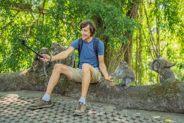 Selfie with monkeys. Young man uses a selfie stick to take a photo or video blog with cute funny monkey. Travel selfie with wildlife in Bali