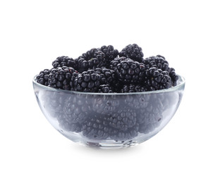 Glass bowl with blackberries on white background