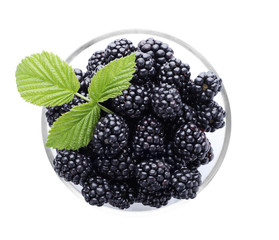 Glass bowl with ripe blackberries on white background, top view