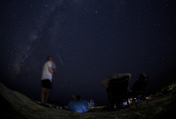 People watch as a meteor streaks past the Milky Way in the night sky during the Perseid meteor shower at Dwejra