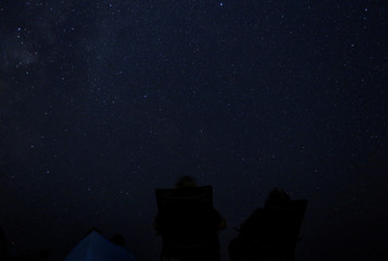 People watch as a meteor streaks past stars in the night sky during the Perseid meteor shower at Dwejra