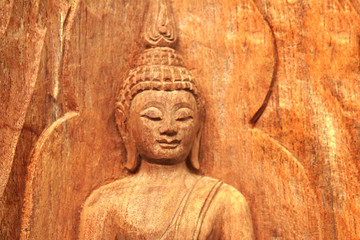 Buddha image carving on wooden background