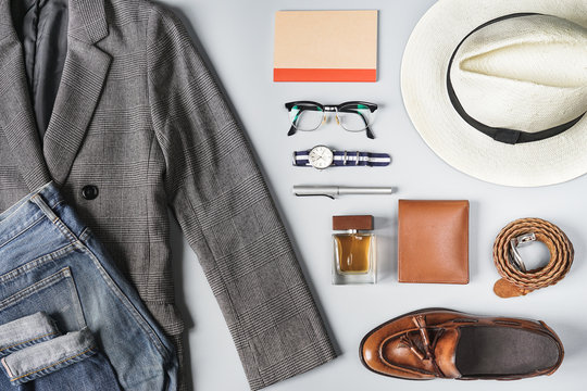 Top view set of classic clothes, plaid blazer, brown tassel loafer and accessories on grey background