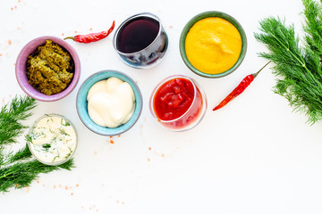 Different dip sauce in bowls near chili pepper and greenery. Ketchup, mayonnaise, mustard, soy sauce, barbecue sauce, pesto, mustard, sour on white background top view copy space