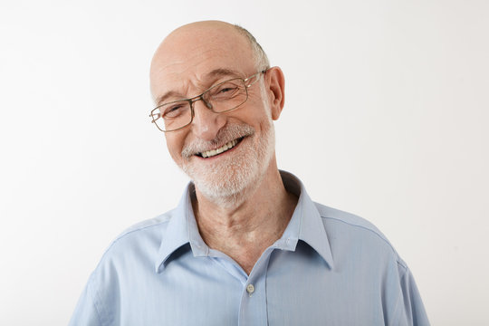 Happy emotional sixty year old man with bald head, gray stubble and wrinkled face having joyful cheerful look, smiling broadly at camera, showing healthy straight teeth. Human feeling and reaction