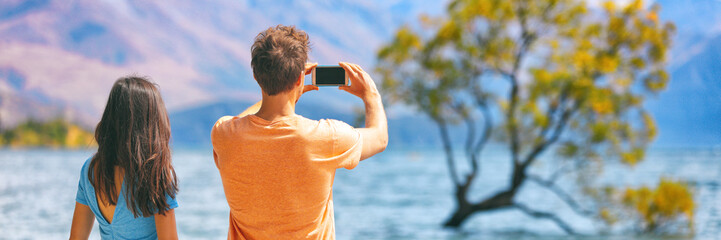 Travel lifestyle people tourists taking picture with phone on New Zealand Wanaka tree background Vacation couple banner panorama.