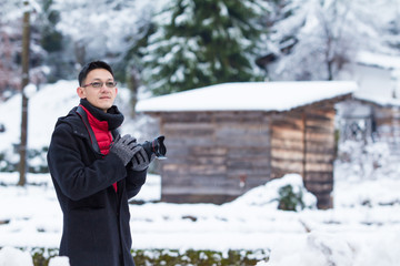 Asian young man taking pictures in winter snow field park Tourist..