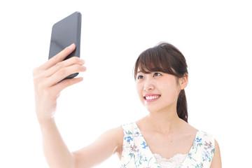 自撮り・ライブ配信をする若い女性