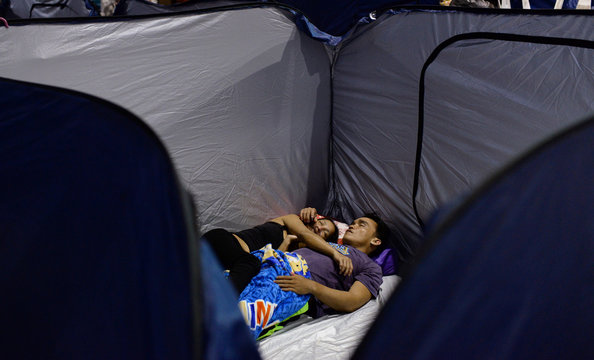 A couple, displaced by flash floods caused by monsoon rains, sleeps at an evacuation center in Marikina
