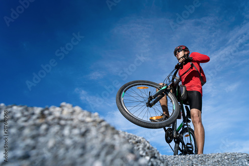Young man riding mountain bike on the background of mountains at young man riding mountain bike on the background of mountains at blue sky voltagebd Image collections