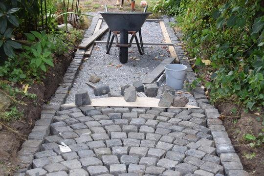 Bauarbeiten an einem Gartenweg aus Kopfsteinen mit Schubkarre und diversem Werkzeug