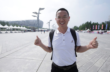 Tan Zheliang poses for a photo after an interview on U.S.-China trade war near the National Olympic Stadium in Beijing