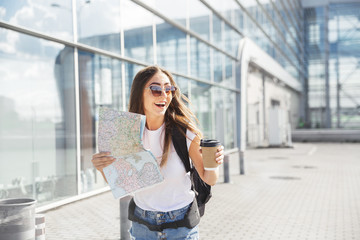 Happy young tourist at airport at window with a map and coffee hurrying to catch a plane.  traveling along Europe, freedom and active lifestyle concept