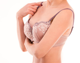 Woman in laced lingerie touching her bra strap, isolated on a white background