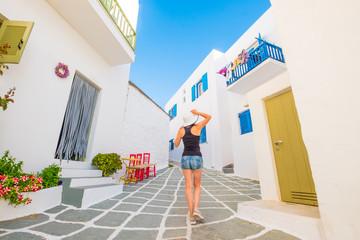 Girl in white hat walking on a typical greek street
