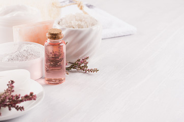 Gentle pink cosmetics oil, small flowers and white soap, cream, clay, towel closeup on white wooden background, copy space.