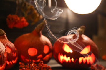 halloween pumpkin lanterns with luminous scary faces and the clouds of smoke in front of them