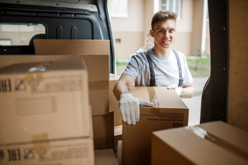 A young handsome smiling worker wearing uniform is standing next to the van full of boxes. House move, mover service.