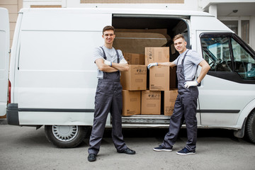 Two young handsome smiling workers wearing uniforms are standing next to the van full of boxes. House move, mover service.