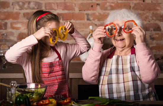 Grandchild with granny holding slices of bell pepper in front of their eyes smiling