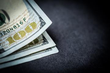 Stack of 100 dollar bills on dark background. Close-up of dollar banknotes on grey background, copy space