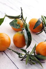 Tangerines with leaves on wooden background. Mandarins Rustic st