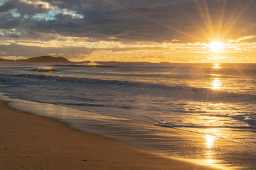 Sunrise over the ocean with star burst around sun