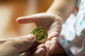 father give money gold coin for baby