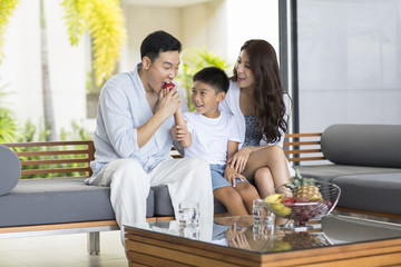 Happy young family eating fruit