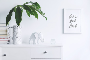 Stylish and modern white interior with mock up frame , elephant figures, stand of books and tropical leaf. White and minimalistic concept of cupboard shelf.