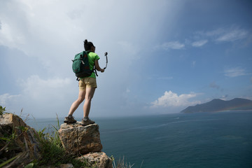 Woman Hiking In Seaside Taking A Selfie With Action Camera