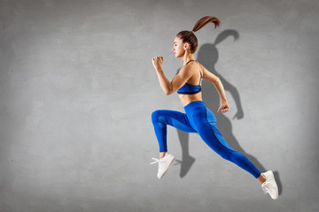 Sporty young athletic woman runing and jumping.