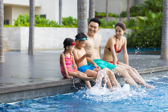 Happy young family sitting side by side at the pool